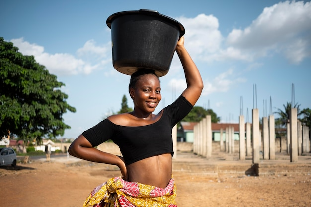 彼女の頭に水のバケツを持っているアフリカの女性
