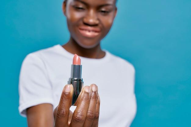 アフリカの女性を保持し、ピンクのリップスティックを示すクローズアップ。