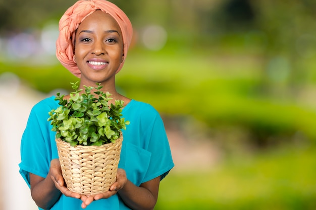 African woman holding plant in vase