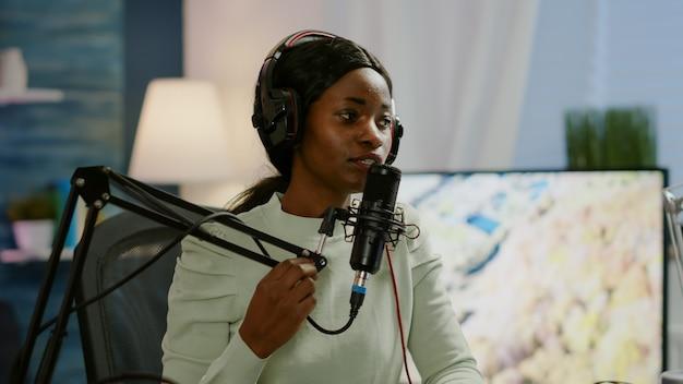 ヘッドフォンを着用してマイクに向かって話しているオンラインショーのアフリカの女性のホスト。ライブストリーミング中に話す、ヘッドホンをつけたポッドキャストで話し合うブロガー、オンエアプロダクションインターネット放送