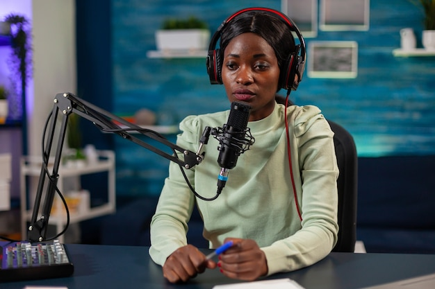 African woman host of online show talking into microphone wearing headphones. speaking during livestreaming, blogger discussing in podcast wearing headphones.