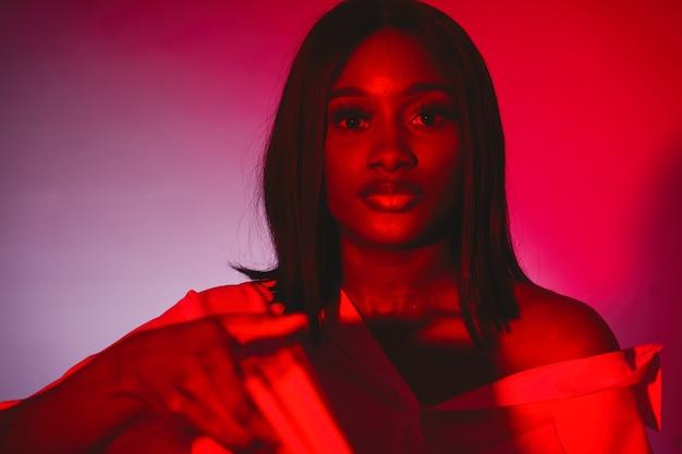 スタジオでアフリカの女性。赤い壁。白いシャツを着た女性。