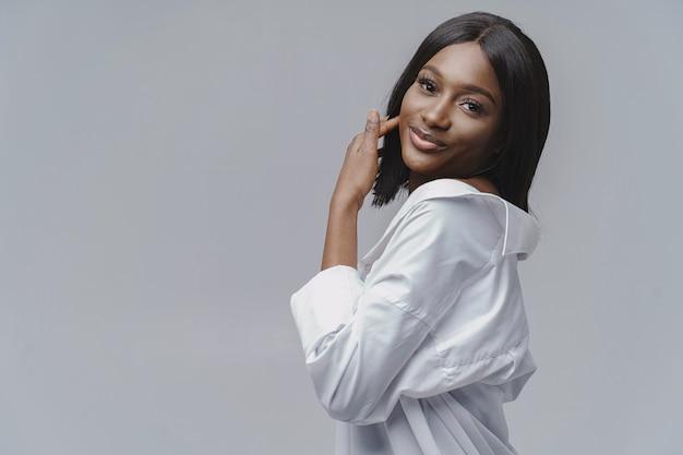 スタジオでアフリカの女性。白い壁。白いシャツを着た女性。