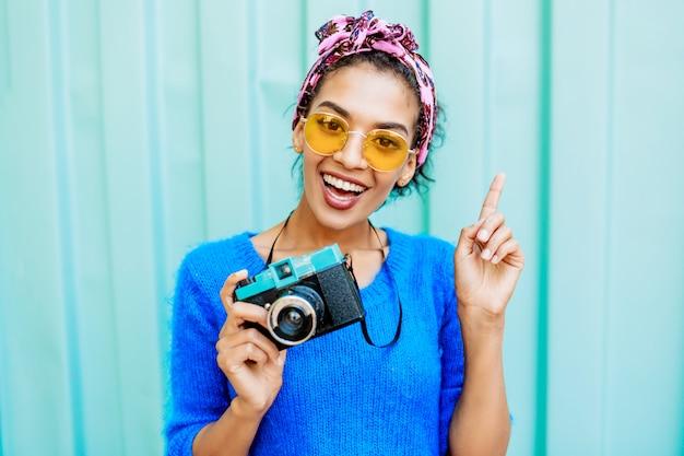 明るいウールのセーターとフィルムカメラを保持している毛にカラフルなヘッドバンドのアフリカの女性。