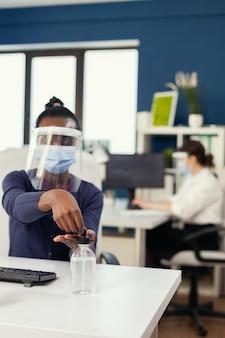 코로나바이러스 동안 얼굴 마스크를 쓰고 손 소독제를 바르는 기업 사무실의 아프리카 여성. 동료들이 백그라운드에서 일하는 동안 소독하는 새로운 일반 직장의 사업가입니다.