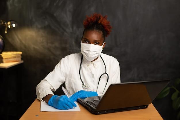 ドキュメントとラップトップとテーブルで医療服を着たアフリカの女性