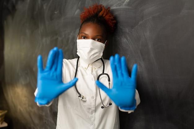 手ジェスチャーで医療制服を着たアフリカの女性