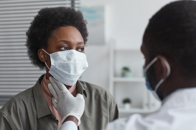 의사가 목을 검사하는 동안 의사의 사무실에 앉아 있는 보호 마스크를 쓴 아프리카 여성