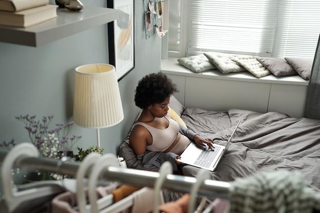 ベッドでラップトップとネットワークの下着のアフリカの女性
