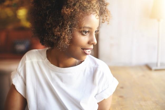 Африканская женщина в белой модной рубашке ждет друзей, чтобы присоединиться к ней в уютном кафе.