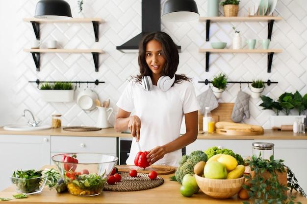 アフリカの女性は台所の机の上の赤唐辛子を切っています。