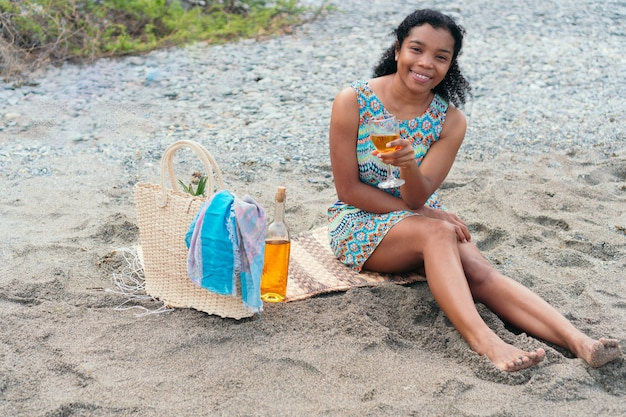 African woman is sitting on the beach with a glass of wine on summer vacation
