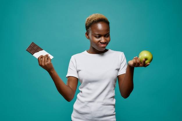 African woman keeping tasty chocolate and healthy apple