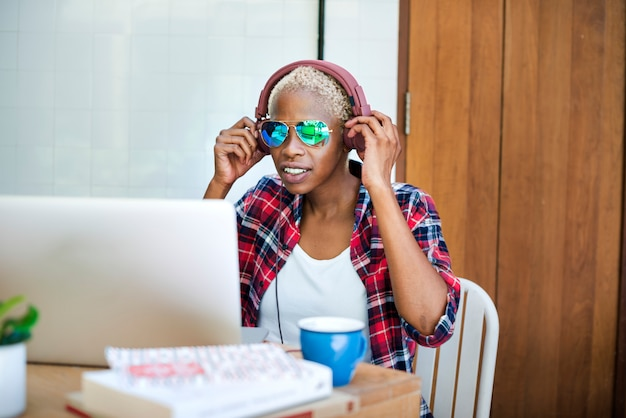 African woman laptop music streaming relaxation technology concept
