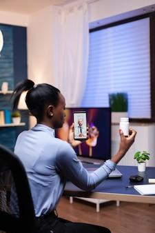 深夜にオンライン相談中に話している医療医師を聞いているアフリカの女性。女性の健康問題について話し合うメディックとのビデオ通話中の黒人患者。