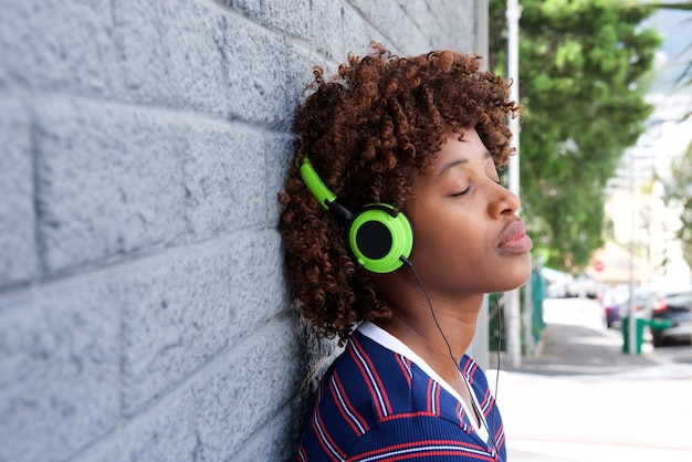 African woman listening to music with headphones