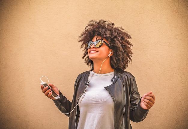 Африканская женщина, слушать музыку со своего мобильного телефона.