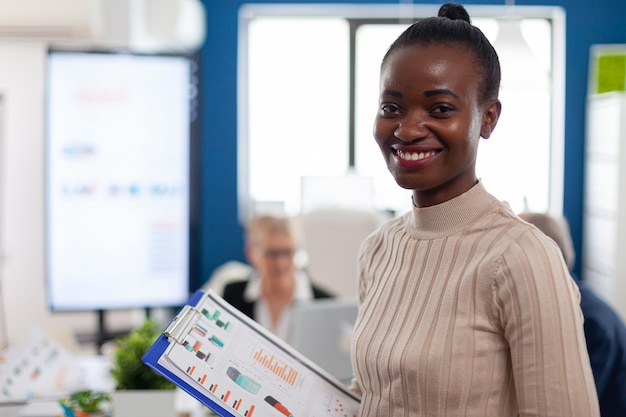 African woman manager looking at camera smiling, holding clipboard, while diverse coworkers talking in background