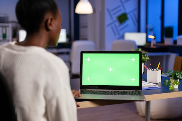 African woman manager working on laptop with green screen mock up, chroma key desktop sitting at desk in business office late at night