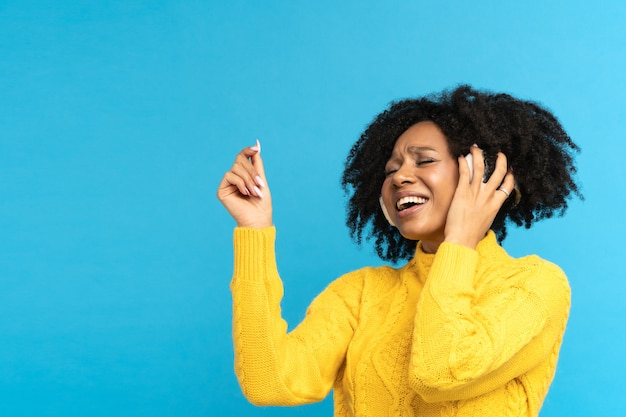 음악을 듣는 아프리카 여성 밀레 니얼은 스튜디오에서 노래하고 춤을 추며 무선 헤드폰을 착용합니다.