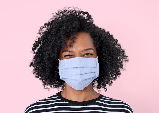 新しい通常のフェイスマスクを身に着けているアフリカの女性のモックアップpsd
