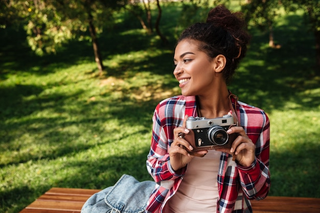 African woman photographer sitting outdoors in park.