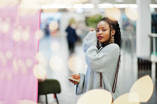 African woman posed in sweater and jeans posed at mall. christmas bokeh and new year theme.