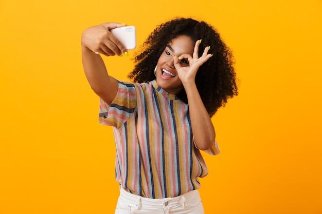 黄色い空間に孤立してポーズをとっているアフリカの女性は、大丈夫なジェスチャーを示す携帯電話で自分撮りを取ります。