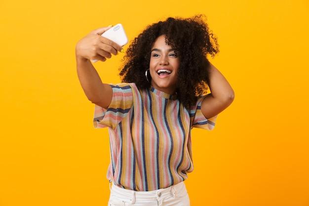 黄色い空間に孤立してポーズをとるアフリカの女性が携帯電話で自分撮りをします。