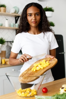 African woman pours out cutted yellow pepper in a glass bowl