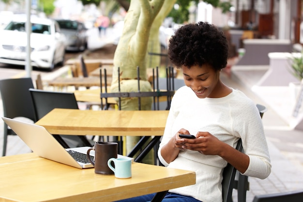 아프리카 여자는 카페에서 휴대 전화에 문자 메시지를 읽고