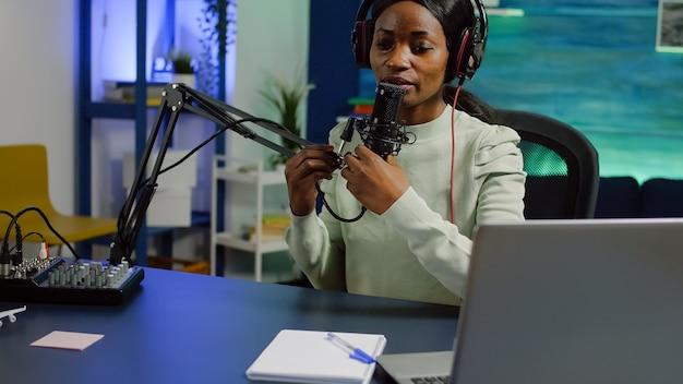 아프리카 여성이 비디오 블로그를 녹화하고 소셜 네트워크를 사용하여 스트리밍 플랫폼에서 콘텐츠를 공유하고 믹서에서 소리를 확인합니다.