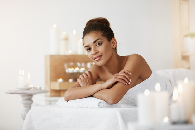 African woman relaxing in spa salon smiling.