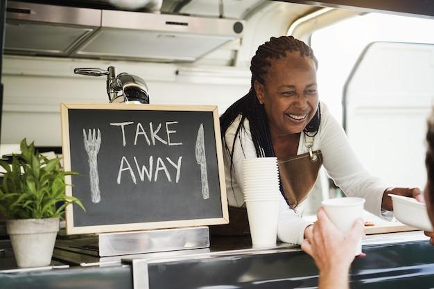 음식 트럭 안에 에코 종이 상자와 테이크 아웃 음식을 제공하는 아프리카 여자-얼굴에 초점