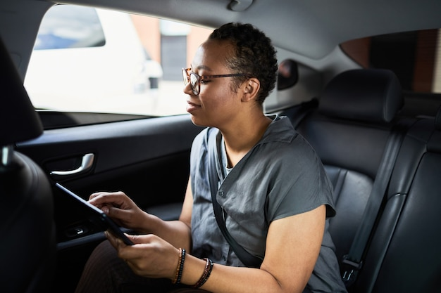 African woman sitting in back seat of the car and working online using digital tablet