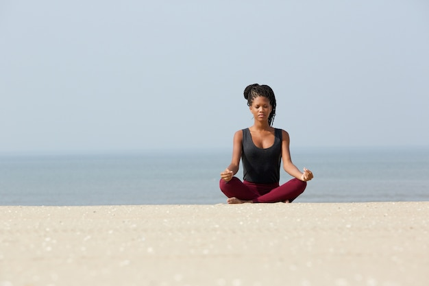 African woman sitting at beach in yoga pose