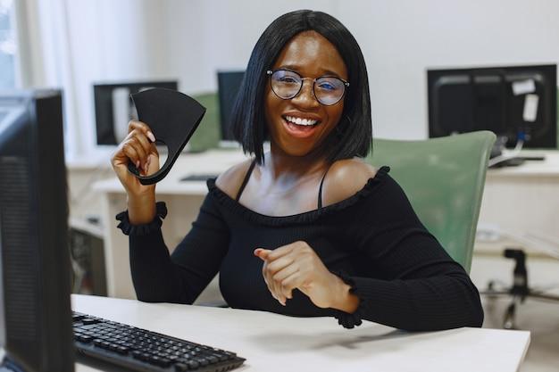 Donna africana che si siede nella classe di informatica. la signora con gli occhiali sorride alla telecamera. studentessa seduta al computer.