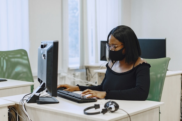 African woman sitting in computer science class. lady with glasses. female student sitting at the computer.