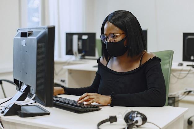 Donna africana che si siede nella classe di informatica. signora con gli occhiali. studentessa seduta al computer.