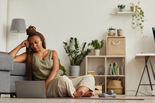 아프리카 여자는 바닥에 앉아 집에서 스포츠 훈련 전에 그녀의 노트북에 스포츠 블로그를보고