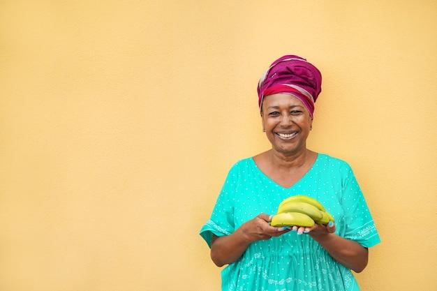 Африканская женщина улыбается на камеру, держа букву бананов