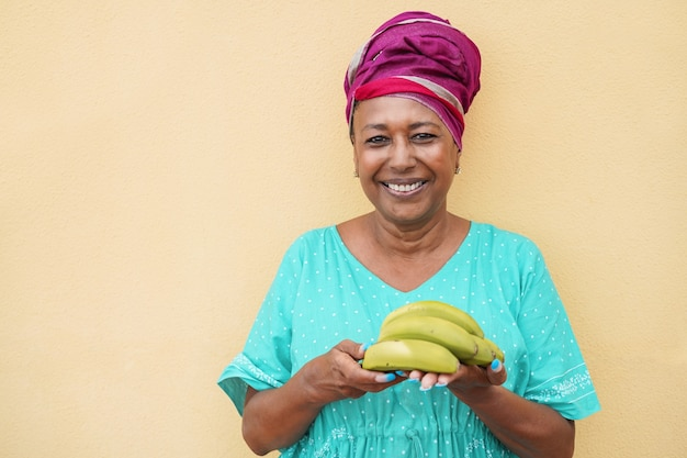 바나나의 무리를 들고 카메라에 웃는 아프리카 여자-얼굴에 초점