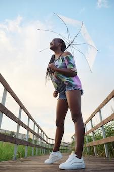 Африканская женщина, стоящая под видом снизу прозрачным зонтиком.