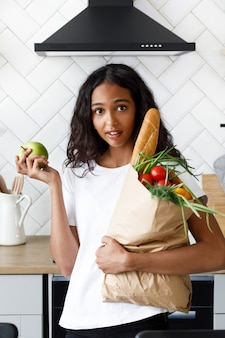 African woman stands on the kitchen holding a paper bag with groceries and has surprised look