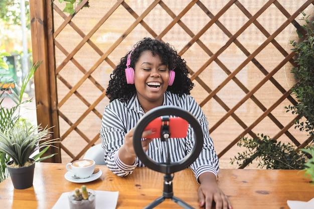 야외 레스토랑에서 휴대 전화 카메라로 온라인 스트리밍 아프리카 여자-얼굴에 초점