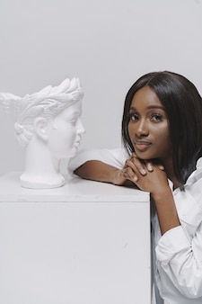 African woman in a studio. white wall.  woman in a white shirt.