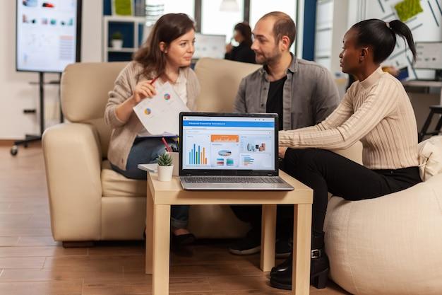 Африканская женщина рассказывает о проекте, обсуждает идеи стартапа, используя ноутбук с графикой, различные сотрудники собрались в процессе совместной работы в компании