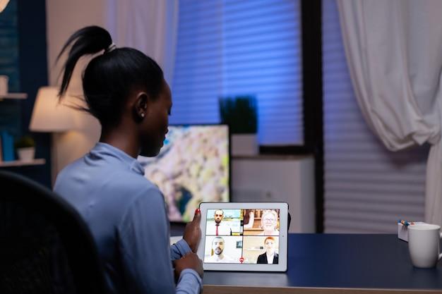 遅いビデオ会議の過程でビジネス顧客と話しているアフリカの女性。仮想会議で話しているネットワークワイヤレスでノートブックを使用している女性。