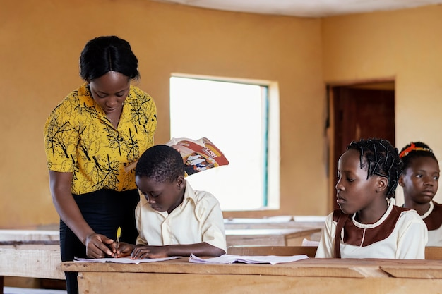 African woman teaching children in class