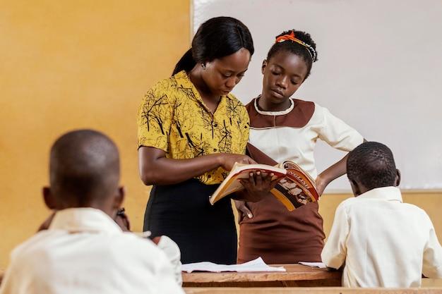 Африканская женщина учит детей в классе